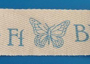 Cinta de letras azules y dibujos sobre tira de algodón natural